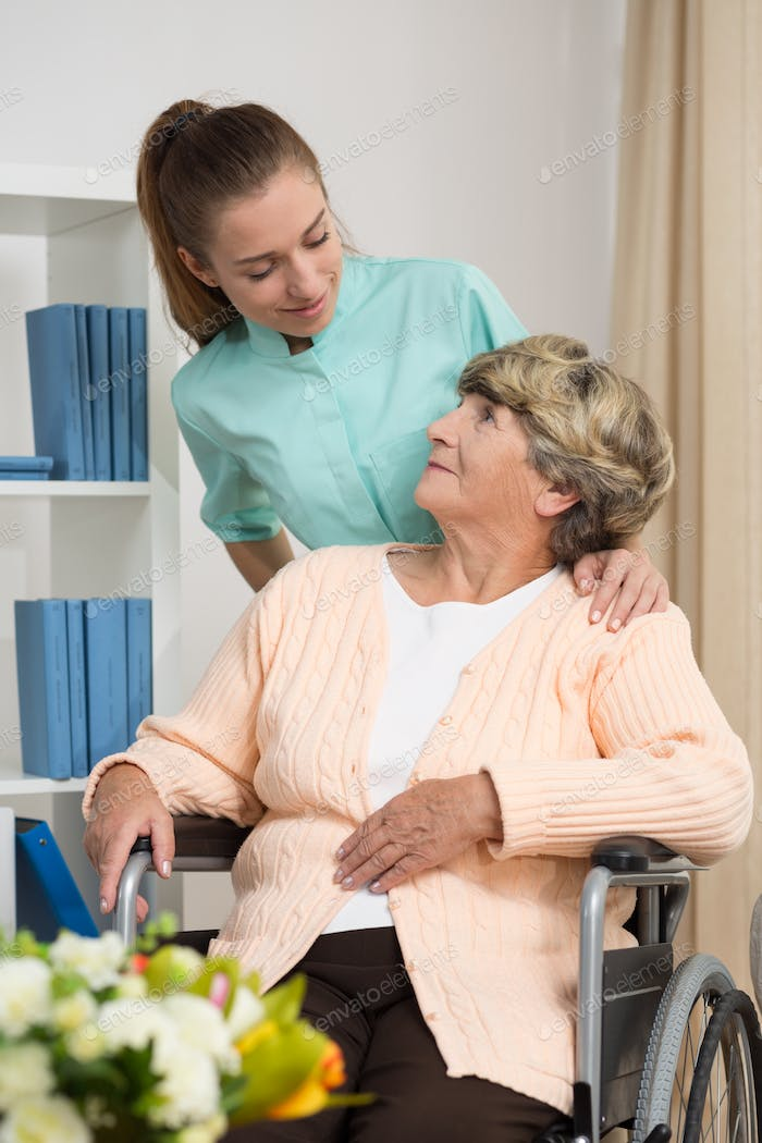 Disabled woman talking with nurse