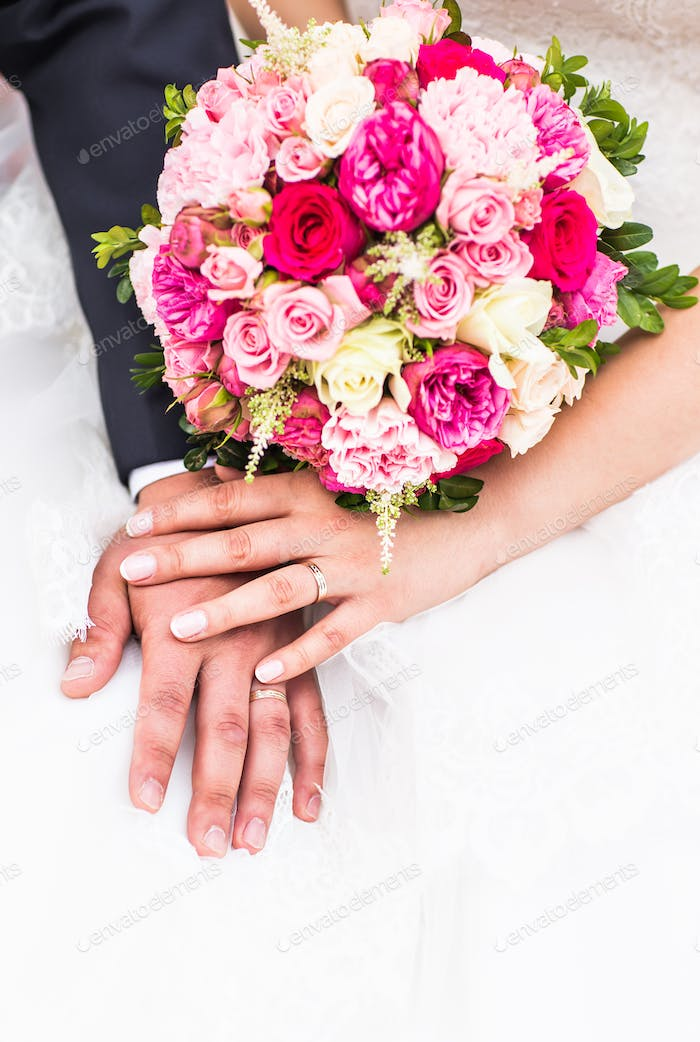 Hands of groom and  bride with wedding rings