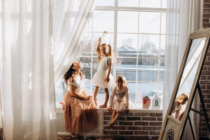 Two little sisters dressed in the beautiful dresses and there young mother sit on the windowsill