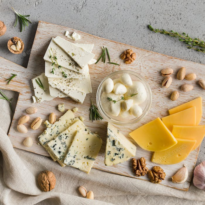 Assortment of cheese with nuts on board