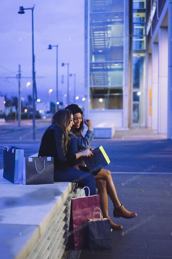 zwei weibliche Freunde beim Einkaufen in einer Stadt in der Nacht