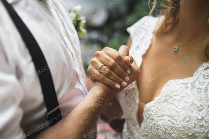 El novio y la novia tomados de la mano juntos. Símbolo de amor y compromiso