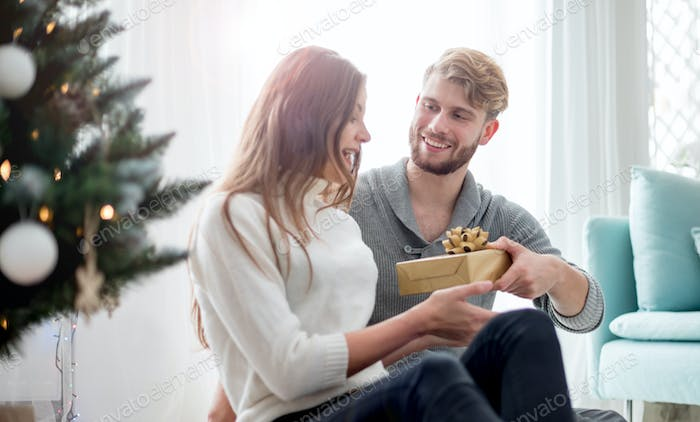 Happy couple are giving themselves Christmas gifts sitting on floor next to Xmas tree