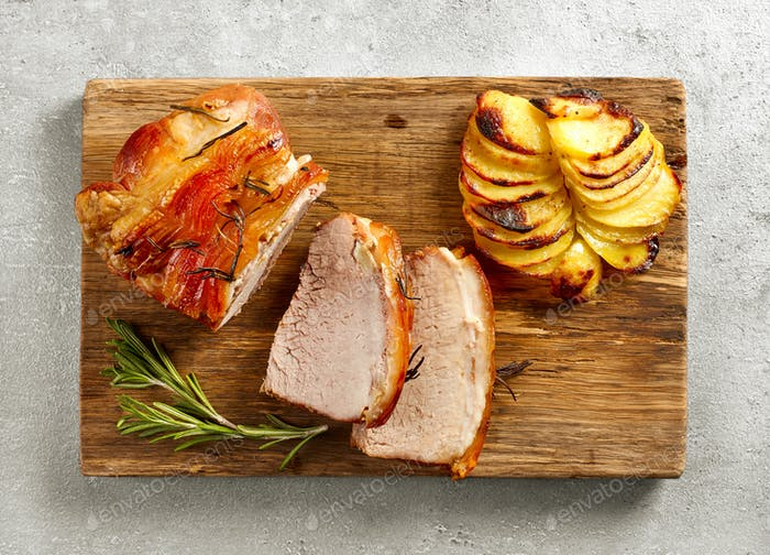 roasted pork on wooden cutting board