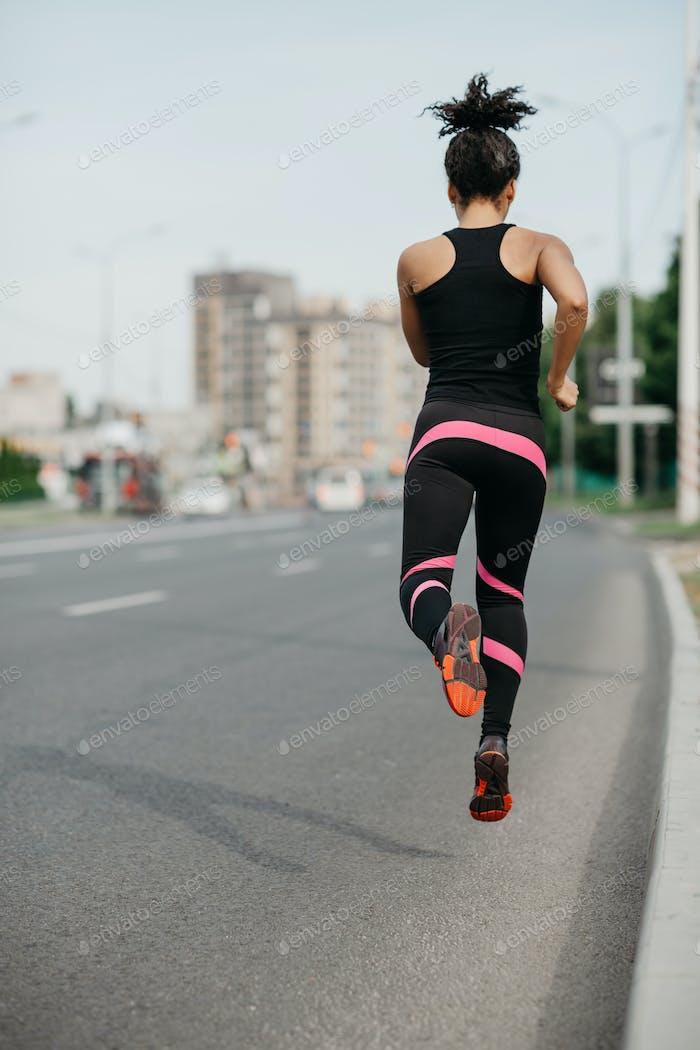 Morning jog on road in city. Muscular girl in sportswear froze in air, jogging
