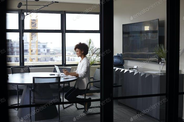 Millennial black businesswoman working alone in an office meeting room, seen through glass wall