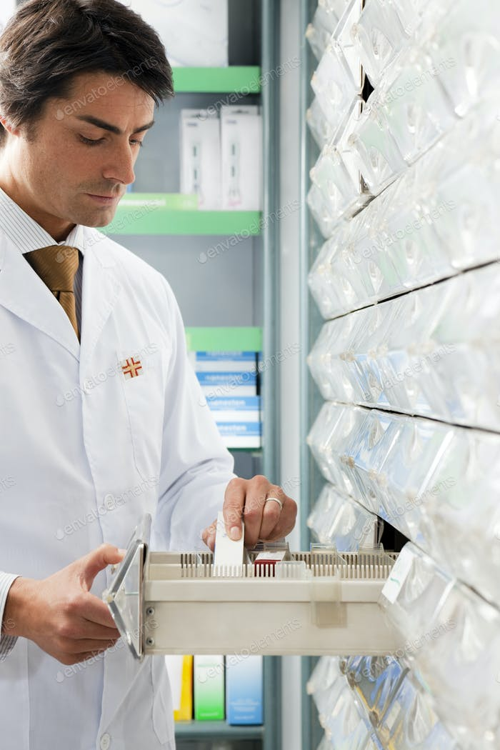Man Working In Drug Store As Pharmacist Putting Medicine In Order