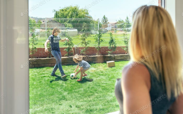 Mother watching her husband and son playing