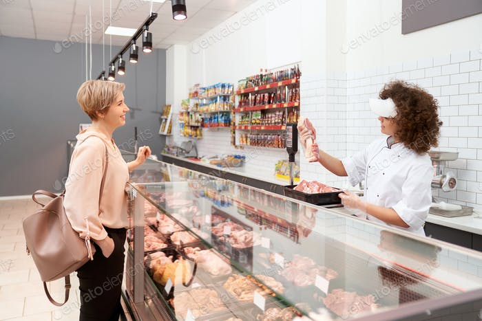 Female butcher demonstrating meat to woman