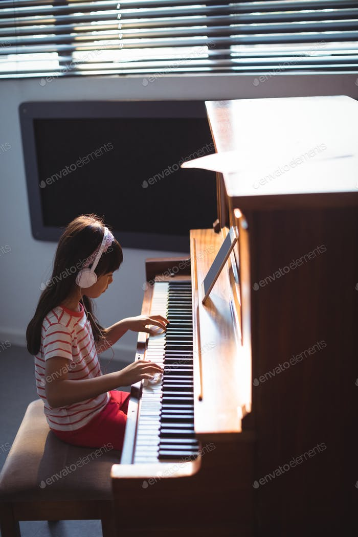 High angle side view of girl wearing headphones while practicing piano
