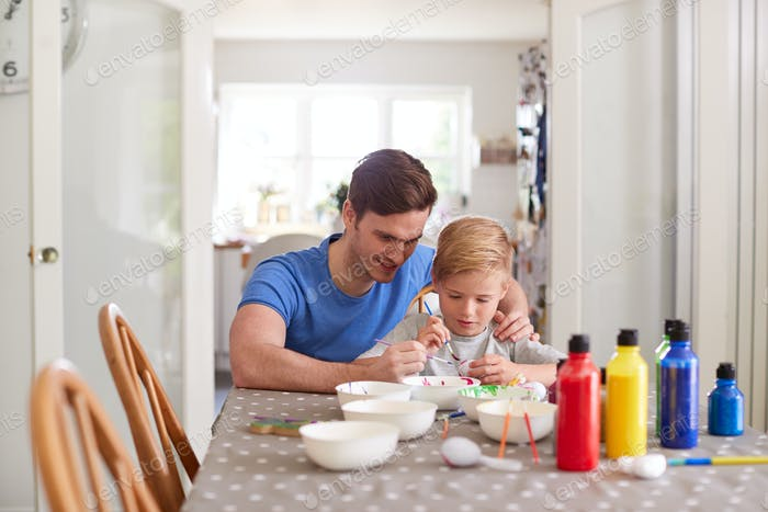 Father With Son Sitting At Table Decorating Eggs For Easter At Home