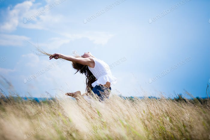 Young woman in casual clothing standing in rye field and enjoying sunshine on summer day with blue