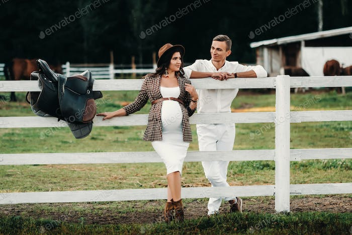 a pregnant girl in a hat and her husband in white clothes stand next to a horse corral at sunset.a