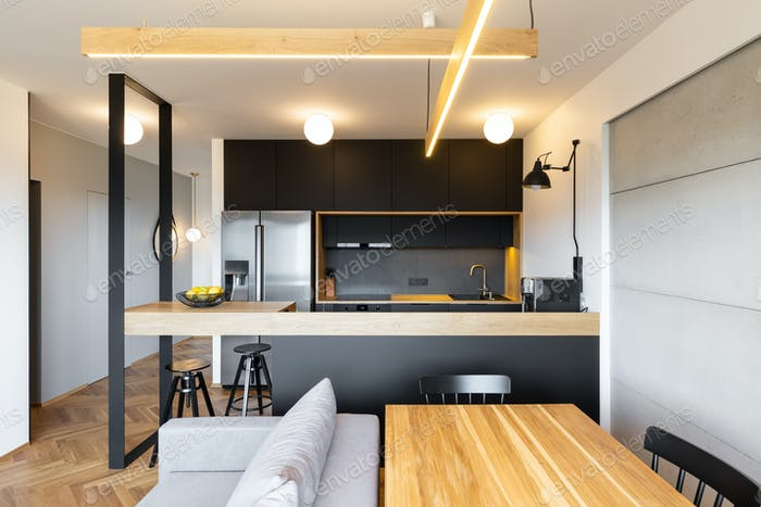 Lights above countertop of black kitchen in open space interior
