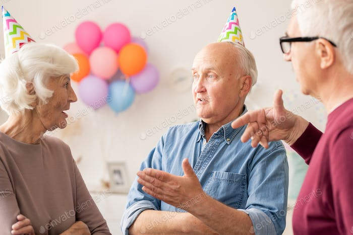Group of senior men and woman talking at birthday party