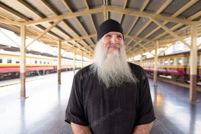 Portrait of mature bearded hipster man thinking at the railway station