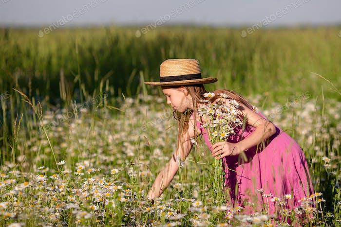 Happy child in field. Beautiful girl in dress in a straw hat