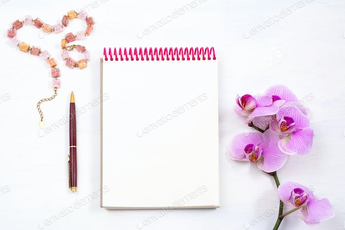 Mockup with notepad, pen and pink orchid, top view