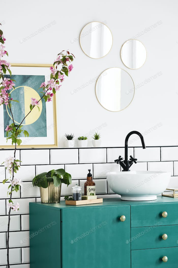 Mirrors and poster above green cabinet in modern bathroom interi