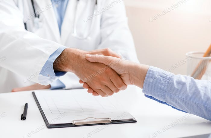 Senior female patient shaking hands with doctor