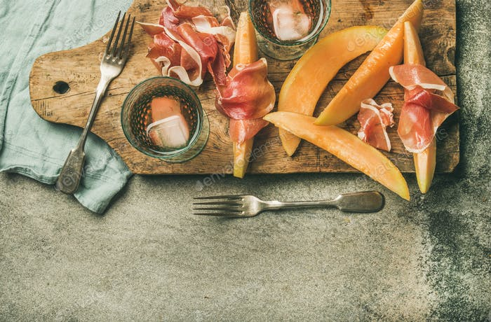 Summer wine party set with rose wine, prosciutto and melon
