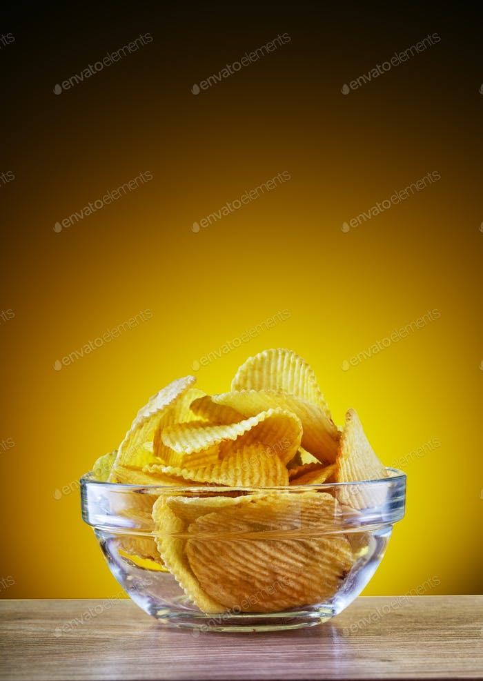 Chips in transparent plate on yellow background