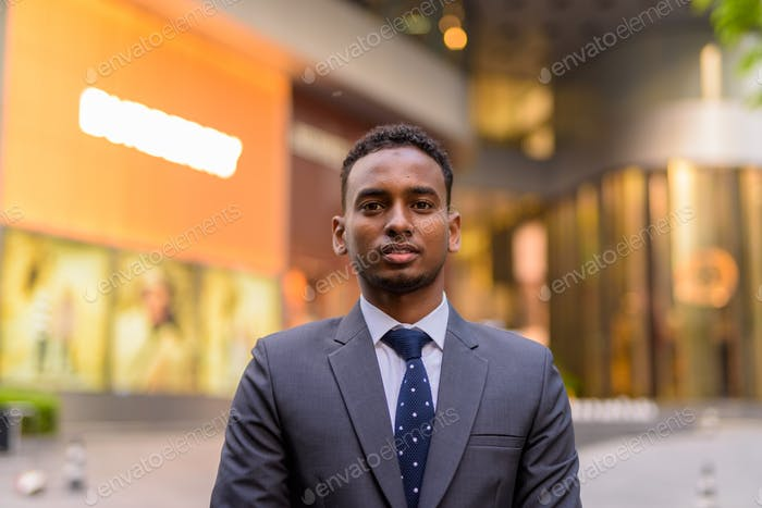 Face of young handsome African businessman outdoors