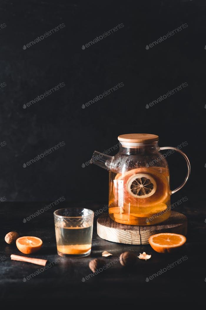 Zitrustee in einer transparenten Teekanne auf dunklem Betongrund. Gesundes Getränk, vegan, Ökoprodukt