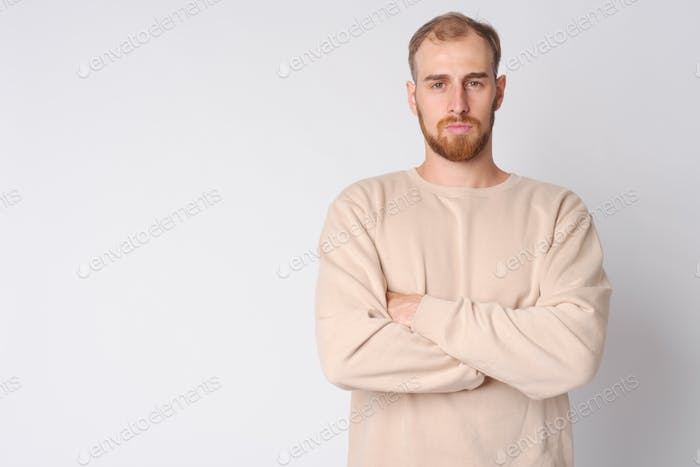 Portrait of young bearded man with arms crossed