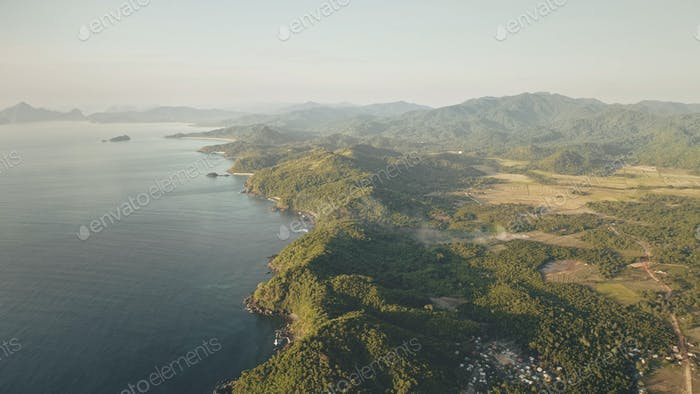 Fog haze over mountains tops at Philippines countryside aerial. Rural buildings, houses at forest