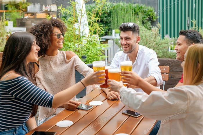 Group of friends celebrating at an open air restaurant