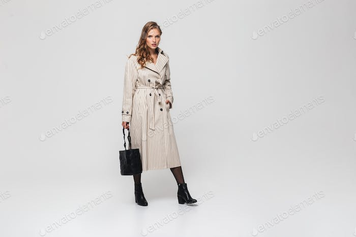 Beautiful woman with wavy hair in striped coat holding black bag thoughtfully looking in camera