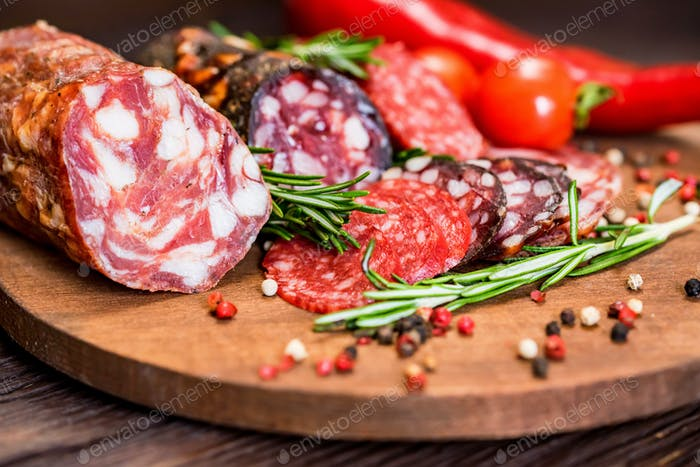 Three sorts of salami with tomatoes and peppercorn