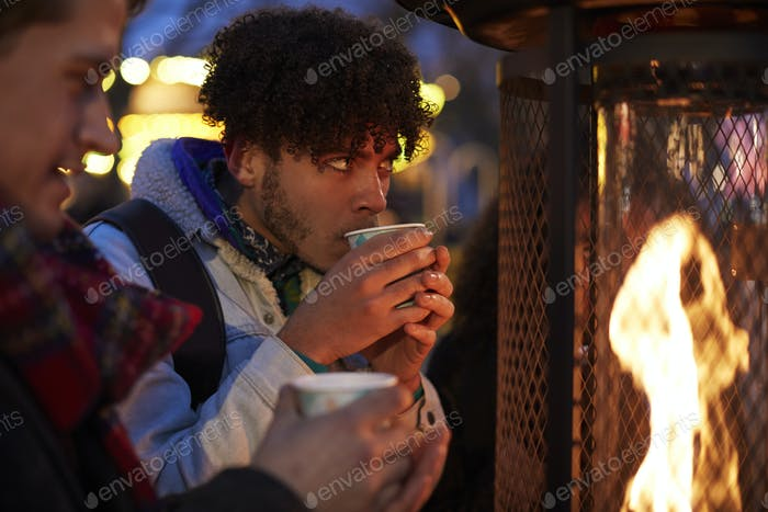 Male Friends Drinking Mulled Wine At Christmas Market