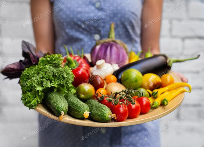 Farmer holding wooden box with crop of vegetables