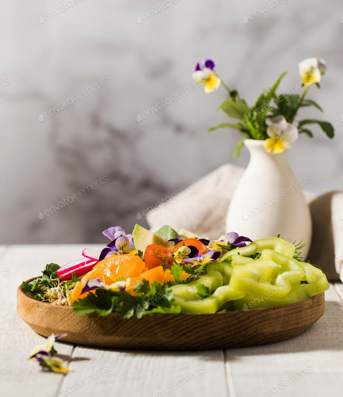Vegetable summer salad decorated with edible flowers. Summer dish, summer menu.