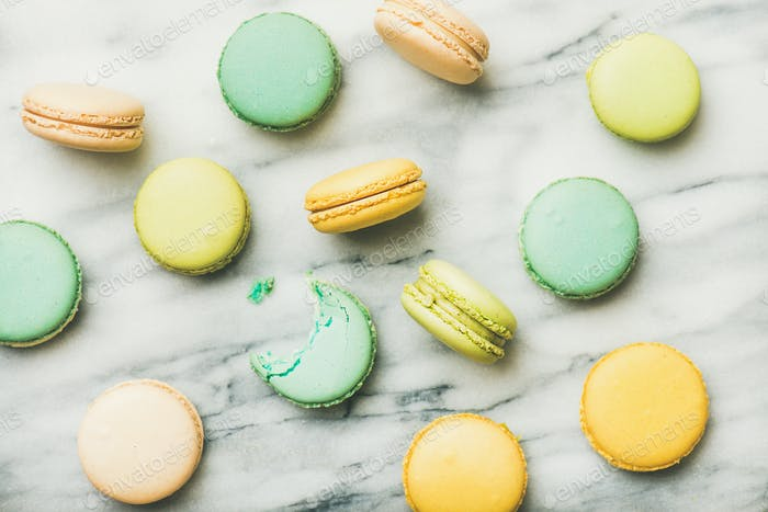 Colorful French macaroons over grey marble background, top view