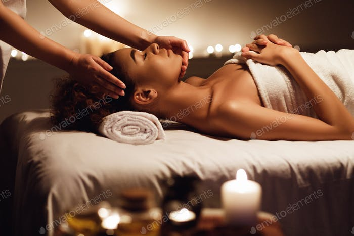 African girl having face massage, relaxing in spa salon