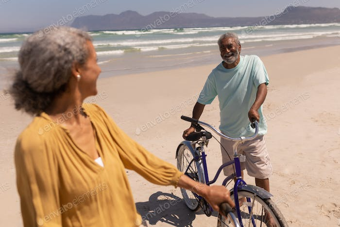 Happy senior couple standing with bicycle and looking each other on beach in the sunshine