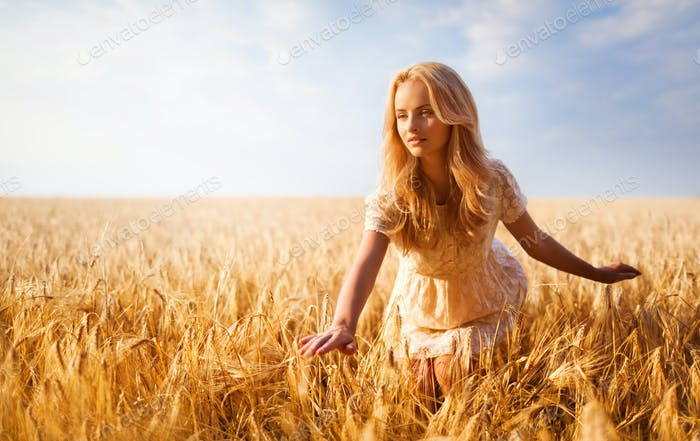 Girl with blond hair posing on wheat field