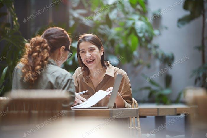 Zwei lächelnde junge Frauen diskutieren Business-Projekt in Cafe