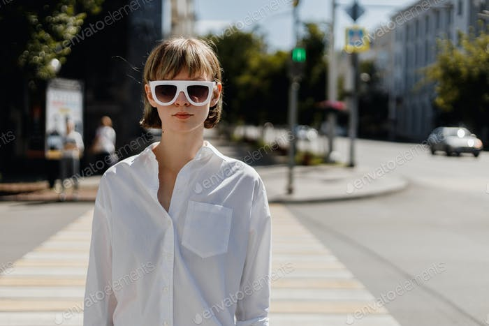 Stylish young woman in white sunglasses dressed in white shirt is standing in the city street on a