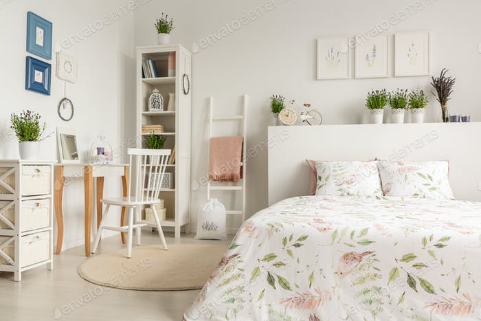 Real photo of a pastel bedroom interior with a double bed, flora