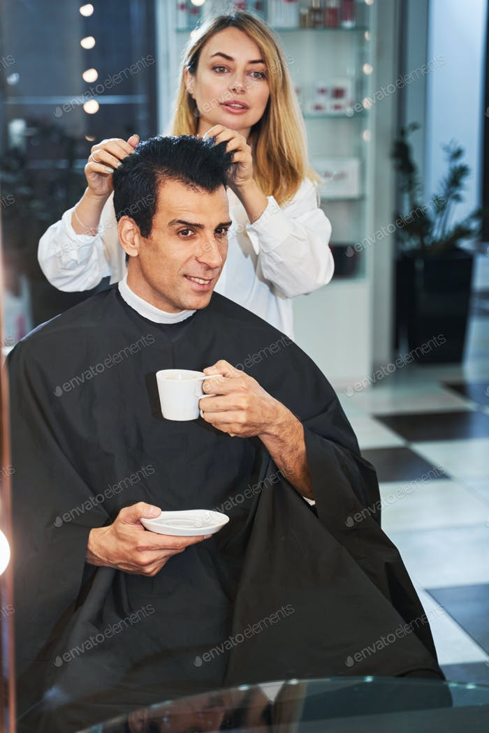 Caucasian client drinking coffee while receiving haircut