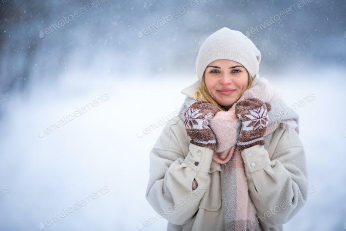 Smiling woman enjoying winter among snow outdoor