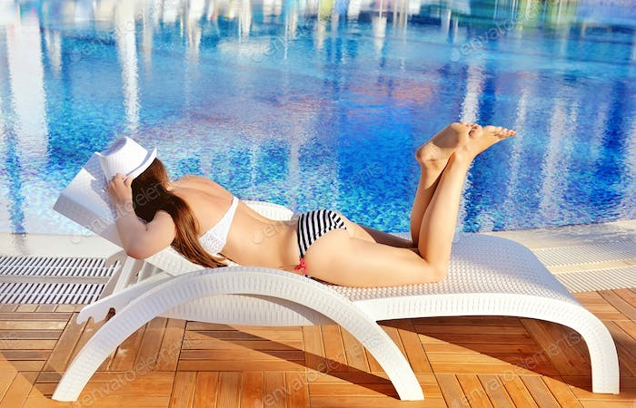 Woman in white hat lying on a lounger near the swimming pool. Su