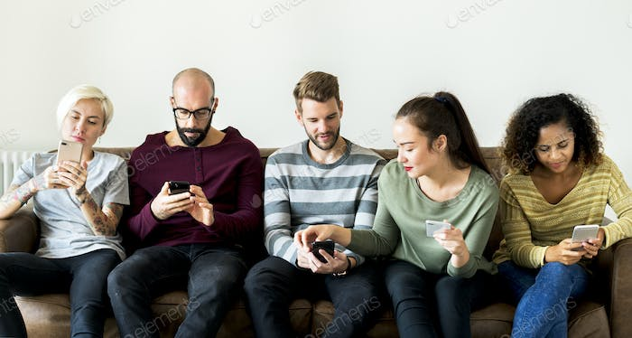Group of people using mobile phone on couch