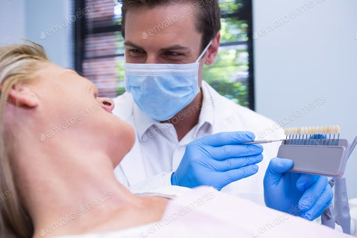 Close up of dentist showing equipment to patient