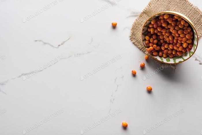 Draufsicht der Schale mit Beeren auf Marmoroberfläche mit Sackleinen