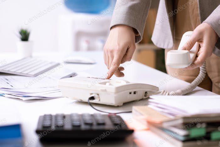 Young elegant office manager or businesswoman pressing button of phone